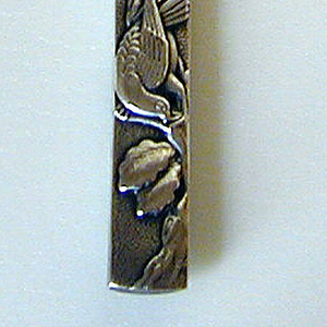 Knife in the form of a Japanese sword; handle with mottled surface, one side decorated with a dove and tree with leaves; other side depicts fish. Flat, curved blade engraved with stylized foliate decoration.