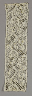 Band of Milanese-style lace in a scroll pattern.