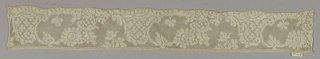 Valenciennes type cap lace. Leaf scrolls and rococo ornament with small quatrefoil motifs.