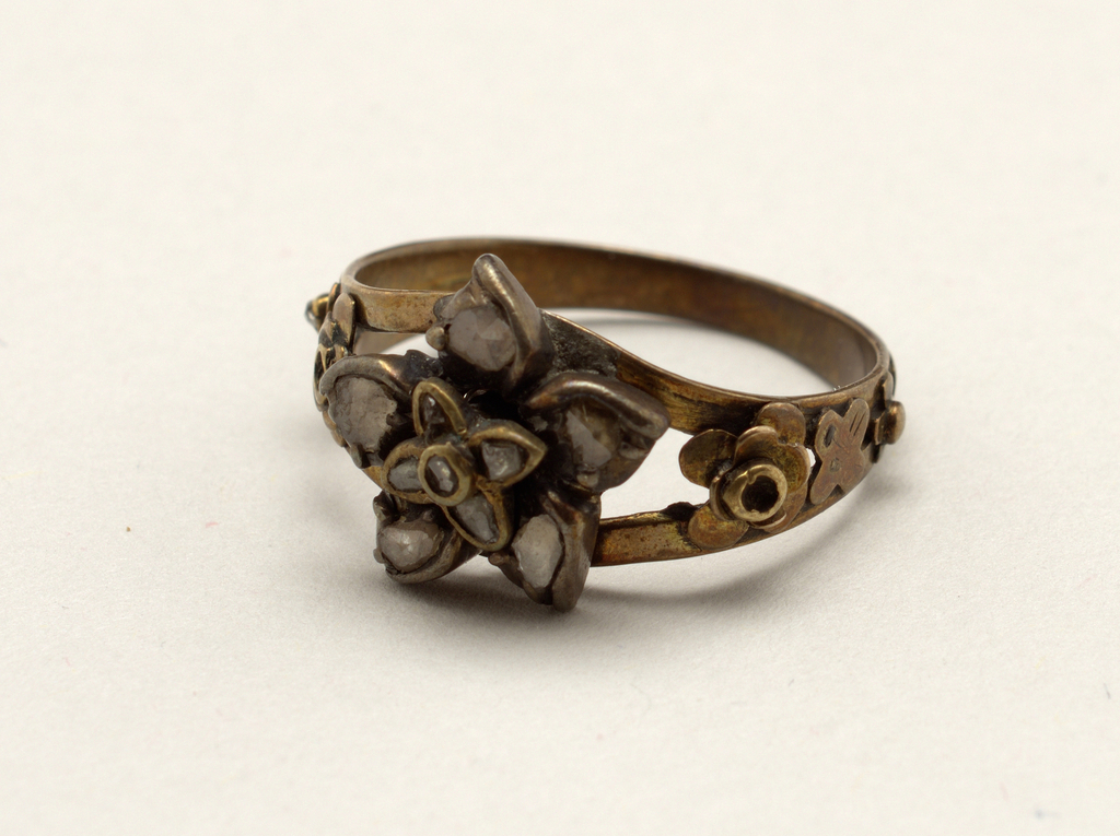 Gold ring separating into two bands on which is an ornament of a flower (made of gold) with petals of rose diamonds.  At the sides of the ring are small flowers with rose diamond centers.  Two small diamonds missing.
