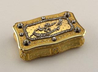 Box and cover with diamond decoration in corners and cartouche framing the central abstract design.  Gold foliate motifs along the periphery of the cover as well as on the sides of the box.  Classical motif on each corner of the box and center of the front separated by rectangular forms encasing small circular pattern.