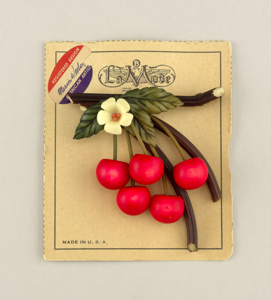 Brooch in the form of five red cherries, green leaves and a white blossom hanging from brown branches; pinned to original display card.