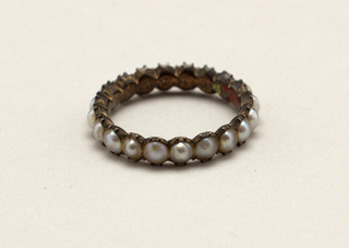 Circle of pearls set in gold band.