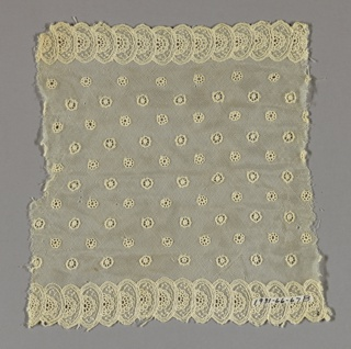 Machine net ornamented with small embroidered wheels scattered over field between two borders of overlapping ovals containing wheels.