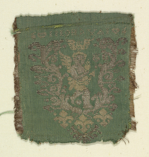 Piece from a pocket or pouch with cupid surrounded by arabesque ornament and three fleur-de-lys. Letters above, written in reverse. Brocaded in gold and silver on a green ground.