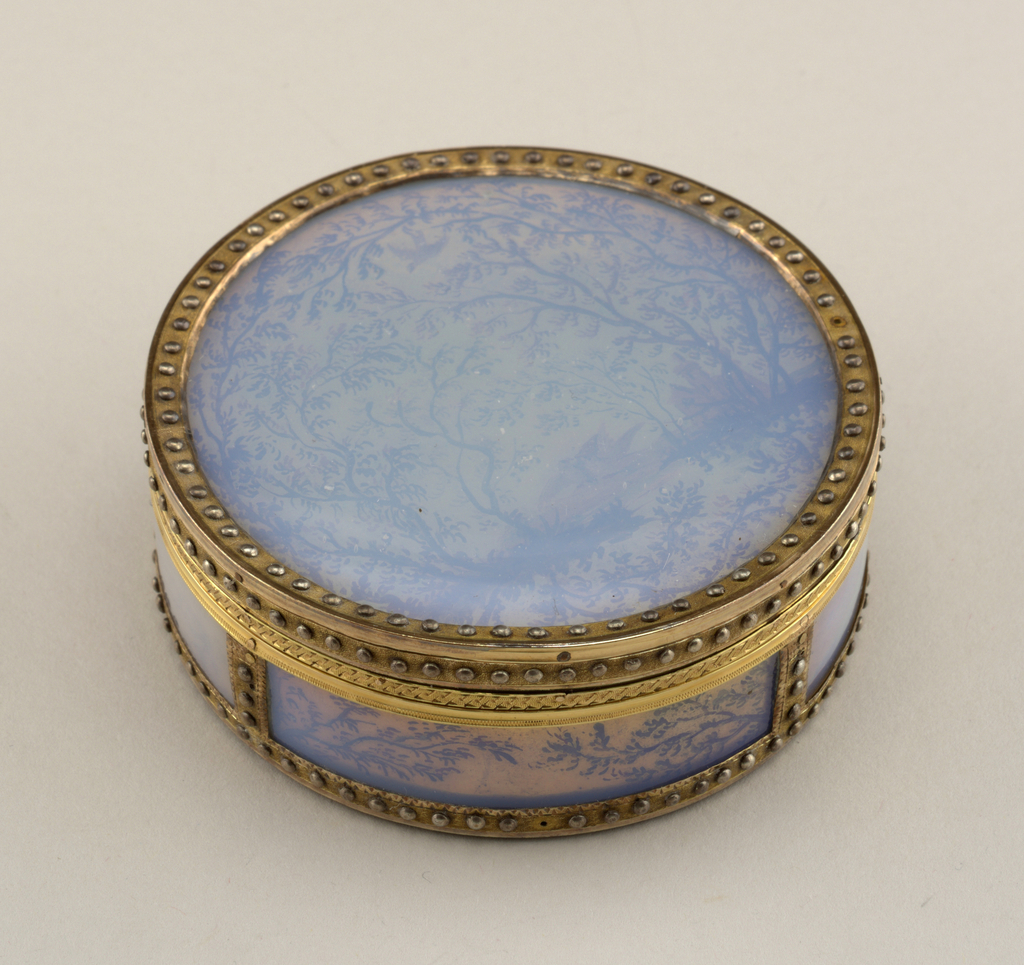 Circular, with detachable cover; gold, the cover, sides and base decorated with silhouette landscapes of trees and birds painted in puce color on silver foil under enamel; matte gold borders studded with small silver bosses; lined with silver foil stamped to simulate engine-turning, under amber-colored horn.