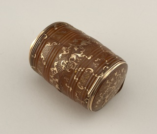 Barrel-shaped blond horn box with hinged lid at each end and center wall dividing it into two compartments. Relief bands encircle box which is decorated with gold piqué posé in patterns of vine leaves, branches, C-scrolls; in gold piqué point are tendrils, draperwork, rays, stippling; gold rims, hinges, and thumbpieces.