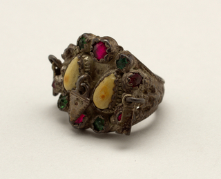Silver ring said to be a memorial to a child. In a silver setting are two teeth surrounded by a ring of green and red paste jewels; one heart-shaped piece and two pieces in design of keys are attached to small rings on the ornament.