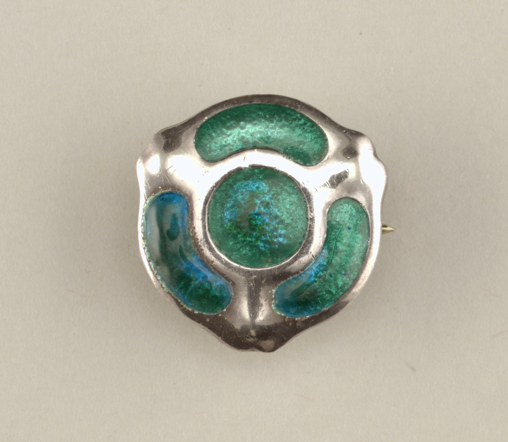 almost circular form with four lobes of green enamel between undulating silver bands