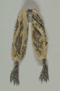 Cream colored silk miser's purse with designs of flowers in cut steel beads.  Tassels are made from cut steel loops.  Single ring of steel, grooved ornament to fasten purse.