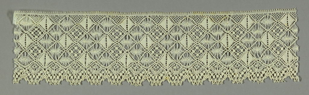 White lace border showing a diamond grid with a variety of fillings and one scalloped edge.