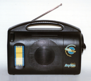 Wind-up radio: black horizontal form with curved handle at top, telescoping metal antenna at top left behind handle; front with rectangular yellow and blue station indicator at left, circular speaker in center, yellow and blue Baygen logos on right; circular retractable crank on right side.