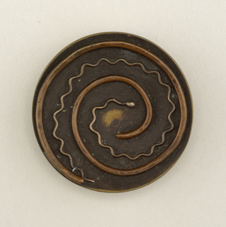 Circular brass disc with spiraling copper and silver wire.