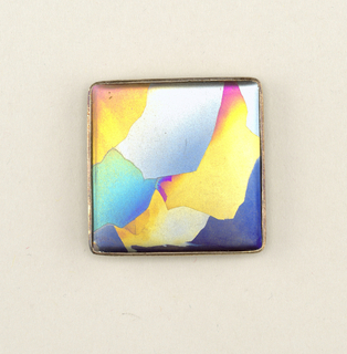 Square in shape, silver backing with clasp and slide loop; front smooth surface with polychrome blotches.