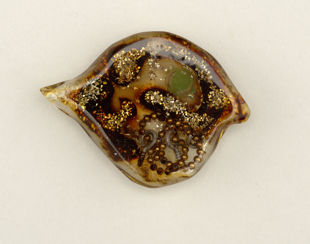 """Clear guppy-shaped brooch with visible interior filled with metal beads, hooked screws, and brown resin in rounded form topped with sprinkling of metal glitter. The """"guppy"""" has one green eye."""