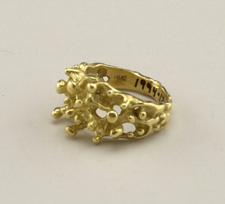 Gold ring with openwork at top and projecting prongs.