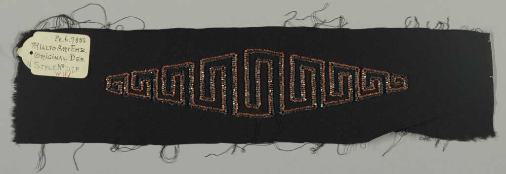Clear amber beads, clear red beads and hematite beads in a modified Greek key pattern, on black crepe ground.
