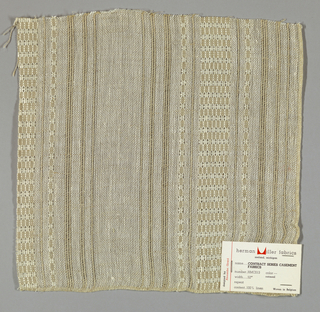 Plain weave in beige and white with leno patterning. Warp threads are both beige and white. Heavy warp threads in white form a leno pattern, which gives a vertical stripe effect. Weft threads are comprised thin beige threads.