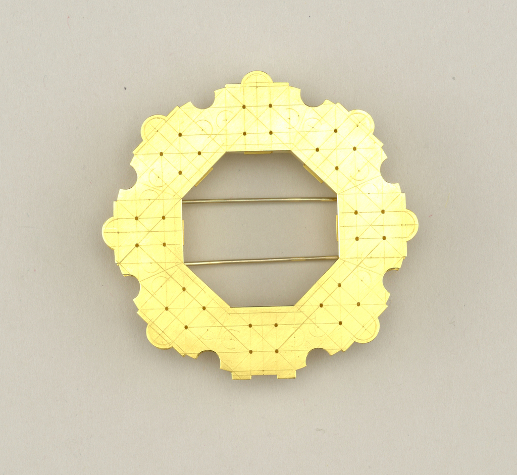 Eight-sided matt-finish open form with curvilinear outer edge and straigt-sided inner edge; the pierced and etched surface devided into geometric units, the whole based on the floor plan of a Palladian villa.  Hinged closure of two straight pins on reverse.