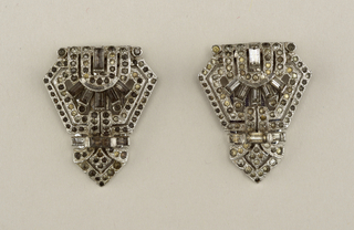 Shield-shaped dress clip comprised of ninety-two brilliant-cut glass rhinestones and nie baguette-cut rhinestones encased in a visible rhodium plated base metal (a less expensive member of the platinum family).   This clip (and it's mate 1997-146-7) are symmetrical, monochromatic and characteristic of the geometric Art Deco style and 'white jewelry' trend sof the 1930s.