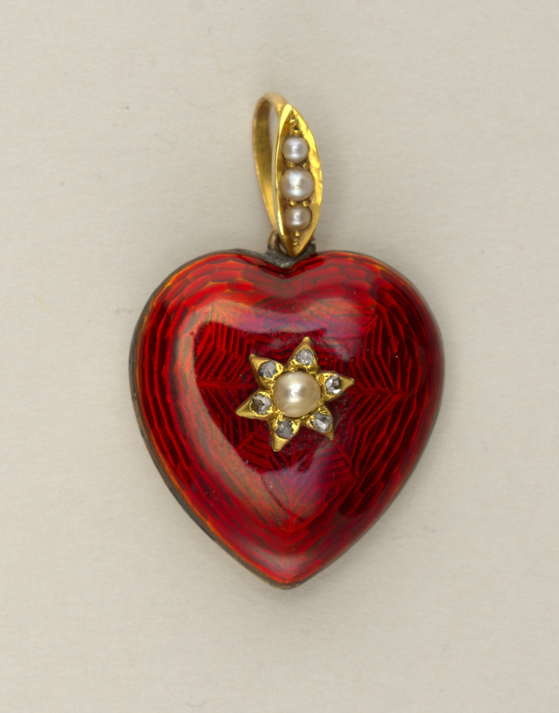 Heart-shaped, enameled red, with pearl and small diamonds at center; on back side a circular locket compartment; loop and ring with three pearlsat top.