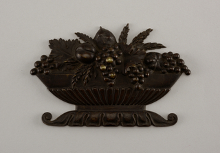 Mount in the form of a basket of fruit. Made of black-patinated bronze.