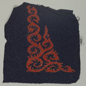 Navy blue crepe ground with red laminated fabric scrolling flame appliqués, secured to ground with whip stitching.