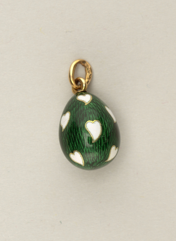 Egg-shaped, enameled with white hearts on dark green background.