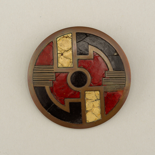 Rectangular brass frame, with red, black, putty-color enamel/composition. Clasp on back side.