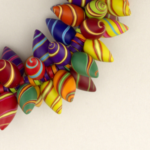 Necklace cord threaded with projecting colorful thorn-like beads, reminiscent of candies with spirals; at the back, knot-like element in black with yellow and red teardrops.
