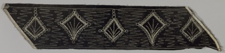 Black velvet border with fan-shaped motifs, loops and zigzags, embroidered in silver metallic chain stitch and accented with silver beads.