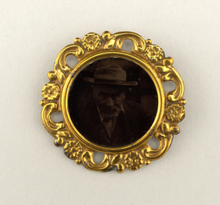Circular; portrait of a man wearing hat (darkened); gilded metal frame of pierced flowers and scrolls.
