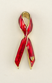Red-enameled form in the shape of a looped ribbon with gold edges and heart-shaped opening at end of right side.