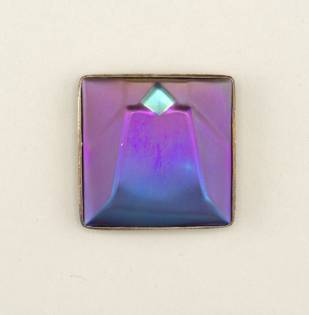Square in shape, silver backing with clasp and slide loop; front with irregular surface in geometric patterns, shading from blue/green to purple.