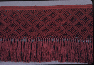 Deep border of red silk macramé with fringe of knotted tassels.