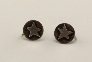 Pair of circular earrings each decorated with slightly irregular five-pointed star.