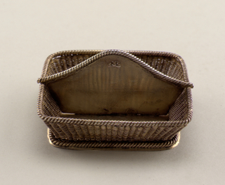Straight-sided rectangle increasing in dimensions toward top. Sides are of basket-woven wire. Two compartments, the longitudinal dividing wall rising to accommodate a pierced handle. Cable trim.
