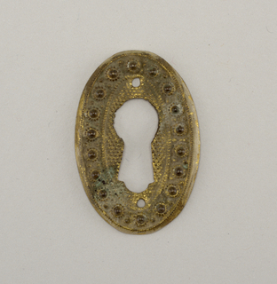 Vertical ellipse. Large keyhole pierced through field of small repoussé dots, surrounded by band of higher relief dots.