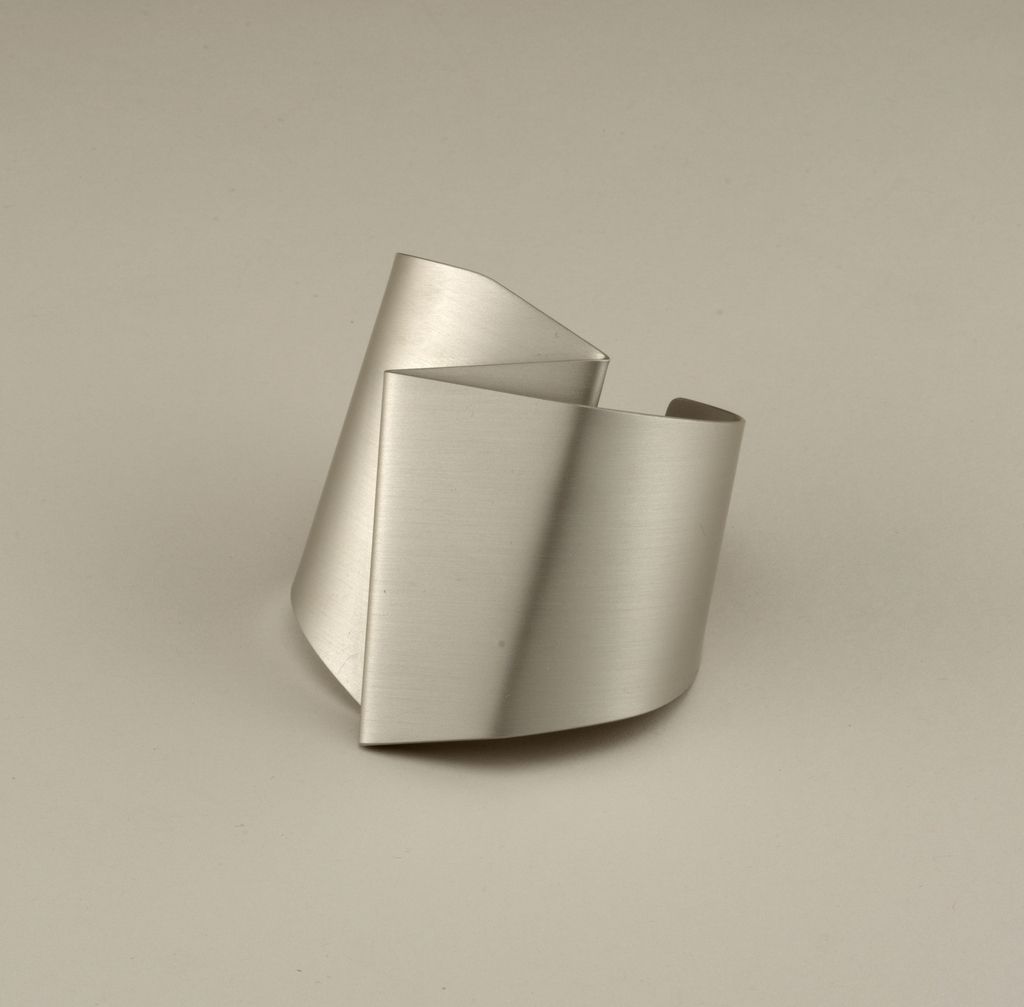 Bronze-colored wide cuff with upper section folded over in angular shape.