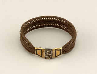 Bracelet of brown-gray hair, elaborately braided, and clasp in three sections of gold, ornamented, on outer sections, with black enamel, on central, with black and white enamel in design of floral spray.