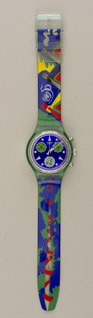 United Nations 50th anniversary commemorative watch. Circular blue face with three circular green chronometers; green bezel; broad flat strap in blue, green, red, yellow, black and white, showing images of clasped hands; green buckle at end of strap.