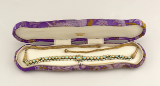 Twenty-one turquoises, eighteen pearls, one hundred forty-eight baroque pearls. Braided gold thread ties.  In embroidered lavender box.
