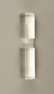Clear perspex cylinder with indented matt-textured section in center; parts a and b unscrew at center.