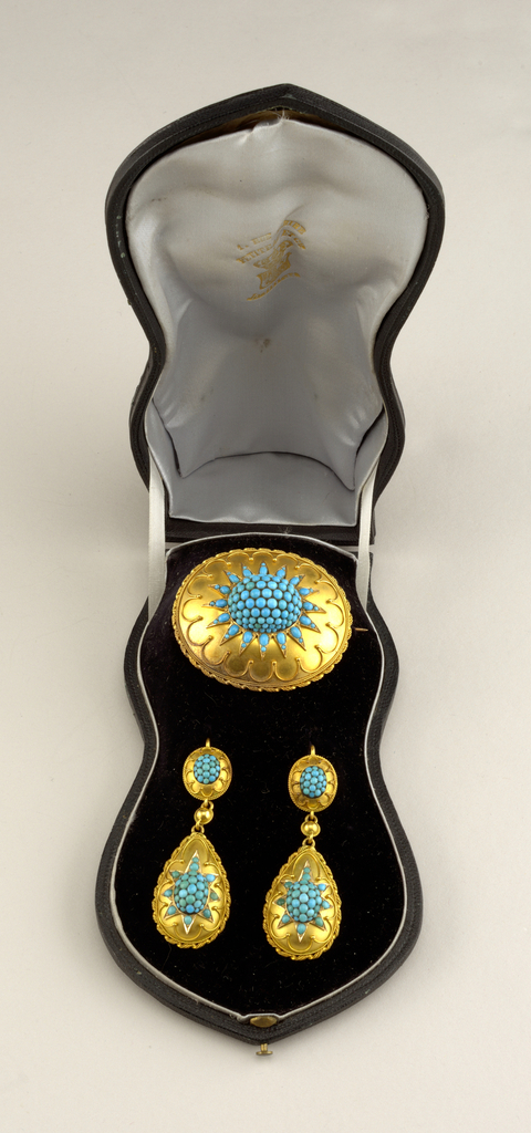 Suite of turquoise and gold jewelry with a bracelet, pair of earrings and a brooch in a fitted box.  By Petiteau et Cie.