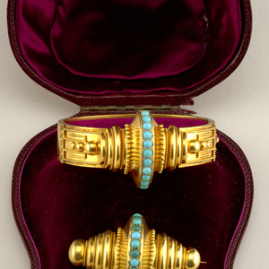 Suite of turquoise and gold jewelry with a bracelet, pair of earrings and a brooch in a fitted box.