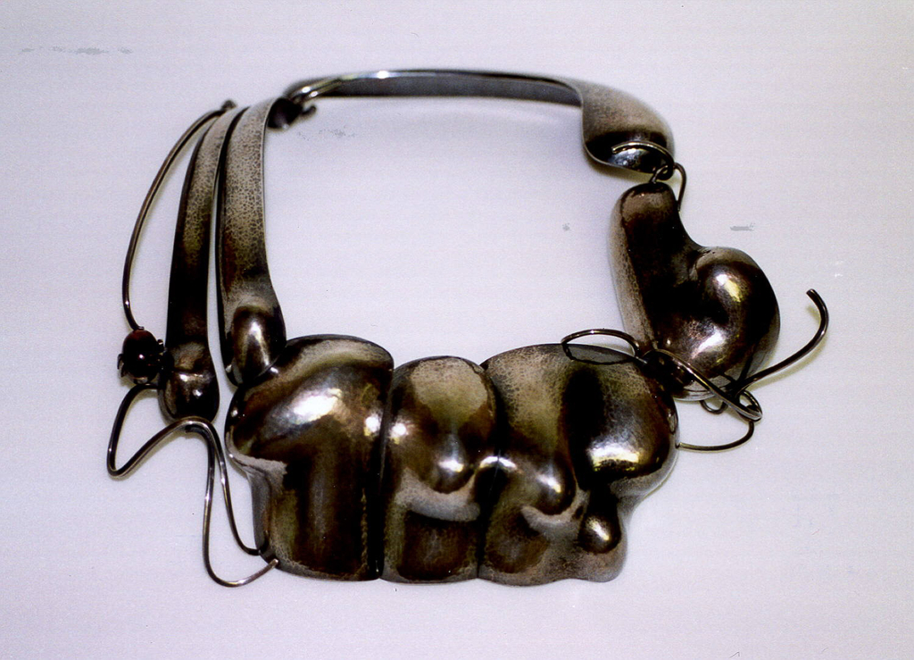 Biomorphic shape in three sections linked to curved wires and oval stone; loop linked together in three parts curved around to be worn on neck.