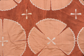 Woven in white and two shades of coral, rows of circular motifs alternating with rows of small crosses.