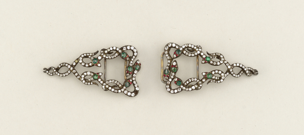 Buckle in two parts: each part is triangular in shape and is composed of entwined snakees (six snakes in each part); bodies studded wtih diamons paste, heads, with emerald and ruby paste.  Buckle is mounted on a pad of white satin, one stone missing.