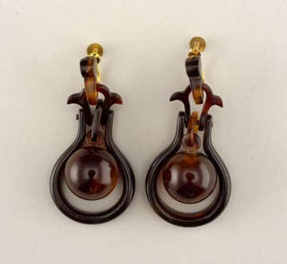 Tortoiseshell pendant earrings. Each earring composed of vertical post from which hangs a stylized tulip, and round pendant surrounded by circular framing.