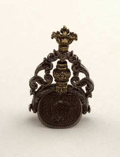 Revolving seal, the three sides engraved with a coat-of-arms showing a crowned cipher surrounded with scrollwork. Handle composed of heavy scrolls and a mask.